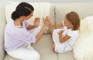 Full length of mother and daughter playing clapping game on couch at home