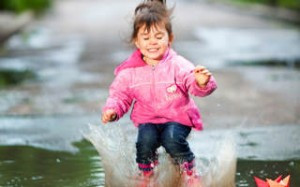 happy little girl, wearing a pink jacket,  jumps into a puddle